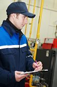 maintenance engineer checking technical data of heating system equipment in a boiler room