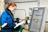 woman engineer checking data of heating system equipment in a boiler room