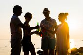 Happy friends drinking alcoholic drinks and having a party on a beach in the sunset. Man in hat enjo poster