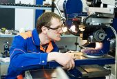 picture of countersink  - worker in uniform and protective glasses working on sharpening machine tool - JPG