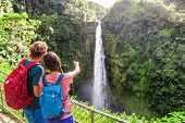 Couple backpacking tourists pointing at Hawaiian waterfall.Tourist girl showing Akaka Falls waterfal poster