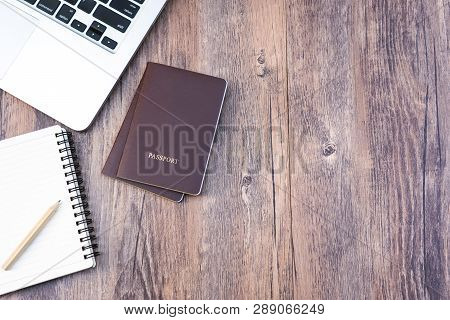 poster of Passport On Wooden Desk Table.travel Planning.top View Of Traveler Accessories With Two Passports, N
