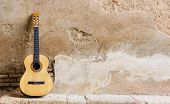 stock photo of acoustic guitar  - Spanish guitar on old wall - JPG