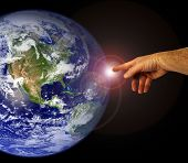 A hand touches the earth. Mankind and peaceful existence.