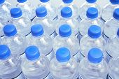 picture of bottle water  - Rows of plastic water bottles with blue caps - JPG