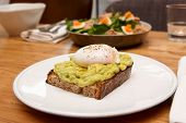 Grilled bread with guacamole and poached egg, tuna salad on restaurant table, breakfast poster