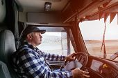Driver In Cabin Of Big Modern Truck Vehicle On Highway poster