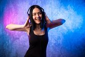 Fashion Pretty Cool Woman In Headphones Listening To Music Over Pink And Blue Neon Background. Beaut poster