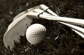 Black and white photo of golf clubs and a golf ball in low light for contrast