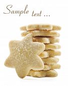 Sugar coated shortbread cookies in star shapes stacked up - on a white background with space for tex