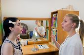 Speech Therapist Teaches A Young Girl The Correct Pronunciation Of Speech On Mirror Background. poster