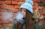 Vape Teenager. Young Pretty White Girl In Blue Cap And Green Jacket Smoking An Electronic Cigarette poster