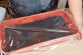 A Woman Covers A Brown Plastic Box With Cellophane Wrap With Planted Seeds Of Plants And Flowers To  poster