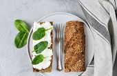 Sandwich From A Cereal Baguette And Cream Cheese And Spinach Leaves On A White Plate.  Light Backgro poster