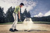 Male golf player in green shirt and grey pants hitting golf ball out of a sand trap with sand wedge