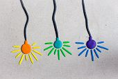 Three Colorful Lamps Of Blue, Violet And Orange Colors Hang On Even Wires Against A Gray Wall. Lamps poster