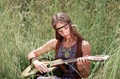 Young Hippie Woman Playing Guitar Sitting On Grass poster