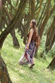 Attractive Hippie Girl Walking Among The Trees In The Forest poster
