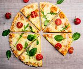 Close Up Of Tasty Sliced Pizza With Tomatoes And Herbs Without One Slice Over Wooden Table Backgroun poster