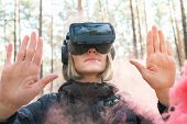 Woman Wearing Virtual Reality Goggles Outside In Forest With Beautiful Pink Smoke Bombs . Vr Glasses poster