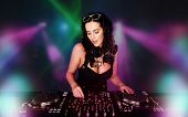 Glamorous sexy busty DJ at work mixing sound on her decks at a party or night club with colourful st