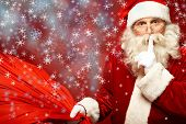 image of shhh  - Portrait of Santa Claus with huge red sack keeping forefinger by his mouth and looking at camera - JPG