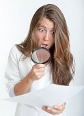 Young woman with a shocked expression examining a document with a magnifying glass