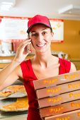 Woman working as delivery girl in a pizza place holding several pizza boxes smiling