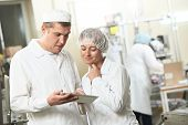 stock photo of pharmaceuticals  - Two pharmaceutical workers discussing manufacture project with tablet computer at pharmacy industry - JPG