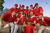 stock photo of clenched fist  - Portrait of excited baseball team holding trophy with pride - JPG