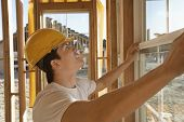 picture of work crew  - Side view of a construction worker in hardhat working on building window - JPG