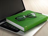 foto of hardcover book  - Laptop green book and glasses on wooden desk - JPG