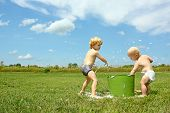 stock photo of soapy  - a young child and his baby brother are playing outside on a summer day with a bucket of soapy water throwing bubbles at each other - JPG