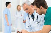 stock photo of conversation  - Group Of Doctors Involved In Serious Discussion With Medical Records - JPG