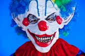 image of clown face  - Scary clown person in clown mask on blue background studio shot - JPG