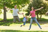 Portrait of a family of three holding hands and jumping at the park
