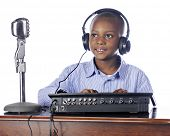 A handsome elementary boy in headphones happily managing a soundboard.  On a white background.