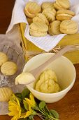 stock photo of shortbread  - Delicious oven fresh baked melting moments shortbread biscuits with sweet filling and daisies in a rustic setting - JPG