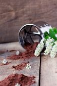 foto of flour sifter  - bird cherry flour with stainless steel sifter on old wooden table with  bird cherry blossoms - JPG