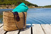 stock photo of dock a lake  - Beach bag with towel standing on a wooden swimming dock at the lake - JPG