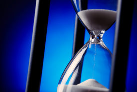 picture of pass-time  - Egg timer or hourglass with blue sand running through the glass bulbs in a concept of passing time and time management - JPG