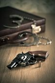 pic of handcuff  - Vintage revolver and bullet with briefcase and handcuffs on background.