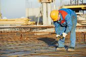 picture of concrete pouring  - builder worker knitting metal rebars into framework reinforcement for concrete pouring at construction site - JPG