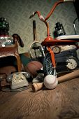 pic of toy phone  - Group of vintage objects on attic hardwood floor including old toys phone and sports items - JPG