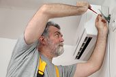 picture of air conditioner  - Electrician installing electrical plug for air conditioner - JPG