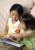 stock photo of storytime  - Two sisters reading a storybook together - JPG