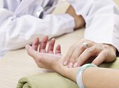 stock photo of hospital gown  - hand of a doctor taking a female patient - JPG