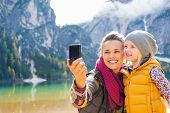 picture of south tyrol  - Happy mother and baby making selfie on lake braies in south tyrol italy - JPG