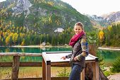 stock photo of south tyrol  - Young woman pointing in information board while on lake braies in south tyrol italy - JPG