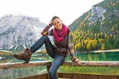 pic of south tyrol  - Portrait of happy young woman sitting while on lake braies in south tyrol italy